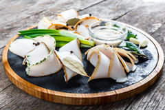Delicious sliced pork fat with spices, green onions, garlic and sauce on cutting board on wooden background Royalty Free Stock Image