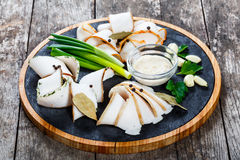Delicious sliced pork fat with spices, green onions, garlic and sauce on cutting board on wooden background Stock Photo