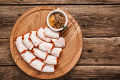 Delicious slices of bacon served on wooden platter. Ukrainian salo served with mustard, top view. Background of rustic wooden table with free space for text Royalty Free Stock Image
