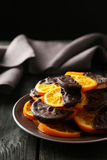 Delicious slices of orange coated chocolate on plate on a black wooden background Royalty Free Stock Photo