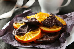 Delicious slices of orange coated chocolate on plate on black wooden background Royalty Free Stock Photos