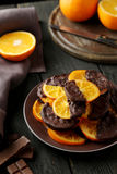 Delicious slices of orange coated chocolate on plate on a black wooden background Stock Photo