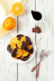 Delicious slices of orange coated chocolate on plate on a white wooden background Stock Images