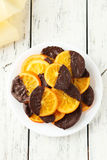 Delicious slices of orange coated chocolate on plate on the white wooden background Stock Images