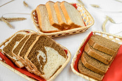 Delicious slicing fresh black, white and colorful bread, in three baskets. Horizontal frame royalty free stock photography