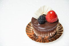 Delicious small chocolate cake with some fruits on top Royalty Free Stock Photography