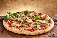 Delicious small pizza with mushrooms and basil royalty free stock photos