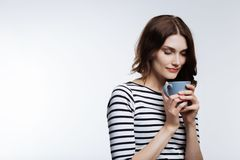 Auburn-haired woman enjoying scent of coffee. Delicious smell. Beautiful young woman smelling the scent of a coffee in a blue cup while standing against a white stock photo