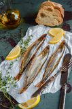 Delicious smoked fish smelt osmerus with lemon and thyme lying on a light colored paper on a wooden background. The vertical frame Royalty Free Stock Photography