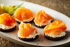 Delicious smoked salmon canapes. On cream cheese or quark garnished with fresh dill and served on an oval platter, close up view Stock Image