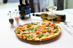 Delicious smoked salmon pizza recipe served with white wine bottle on soft focus stock photos