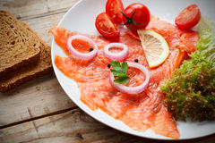 Delicious Smoked Salmon on plate. Smoked Salmon on plate, with cherry tomato, lemon and onion Royalty Free Stock Photography