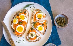 Delicious smoked salmon sourdough toast with goat cream cheese and cut boiled egg, garnished with dill, chives & pickled Capers royalty free stock photos