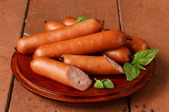 Delicious smoked sausages on a wooden plate Royalty Free Stock Photography