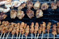 Barbequed food of satay, prawns and chicken wings stock image