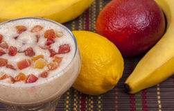 Delicious smoothie of banana. Exotic tropical delicious smoothie of banana, orange, lemon and candied fruit Royalty Free Stock Photo