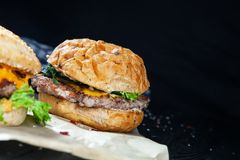 Close up view on burger with meat, sauce and greens on craft paper on a dark background. royalty free stock image