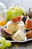 Delicious snack cheese, figs and grapes. Cheese with fruits on a tray, selective focus Stock Image