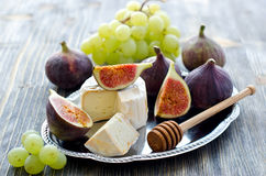 Delicious snack cheese, figs and grapes. Wooden background. Cheese with fruits on a tray, selective focus Royalty Free Stock Photos