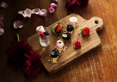 Delicious snack food in brown rustic table with flowers. With cherry chocolate and some more ingridients royalty free stock photo
