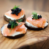 Delicious snack with salmon. Close up of canapes with salmon and caviar Stock Photos