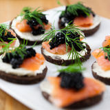 Delicious snack with salmon and caviar. Close up of canapes with salmon and caviar Royalty Free Stock Image