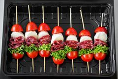 Delicious snacks with cherry, meat and mozzarella in a lunch box. Top view. Concept for food, catering, restaurant, party.  stock photography