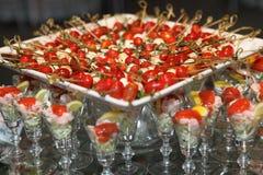 Delicious snacks. Shrimp cocktail next to a tray of tomato mozzarella skewers Royalty Free Stock Photos