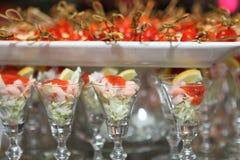 Delicious snacks. Shrimp cocktail next to a tray of tomato mozzarella skewers Stock Photo