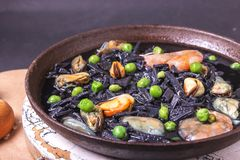 Delicious soup from black homemade noodles made of cuttlefish ink with mussels, shrimps and green peas. Italian cuisine stock image