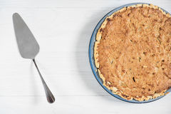 Delicious sour cream pie with a spatula on a wooden light backgr Royalty Free Stock Photos