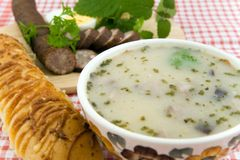 Delicious sour soup with egg, sausage and bread. Sour soup with egg, sausage and bread - traditional polish meal Stock Photography