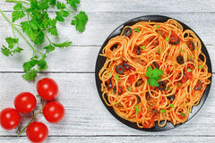 Delicious Spaghetti alla puttanesca with capers. Olives, anchovies, tomato sauce sprinkled with parsley on black plate on wooden table, authentic basic recipe Stock Photos