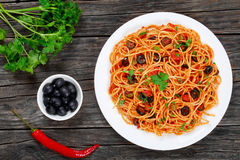 Delicious Spaghetti alla puttanesca with capers. Olives, anchovies, tomato sauce sprinkled with parsley on white plate on wooden table with ingredients Stock Images