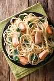 Delicious spaghetti pasta with salmon and spinach closeup on a p. Late on the table. Vertical top view from above Stock Photo