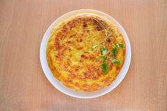 Delicious spanish omelette. High angle view of a spanish omelette with eggs potatoes and onion with parsley leaf on the top over a wooden table Stock Photography
