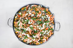 Delicious spanish paella rice with prawn, mussels, squids in pan. Served on table royalty free stock images