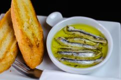 delicious Spanish snack, fresh fish marinated in olive oil, served with croutons stock photo
