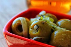 Delicious Spanish tapa. Olives with onion, oregano and olive oil. Served in red bowl Stock Image