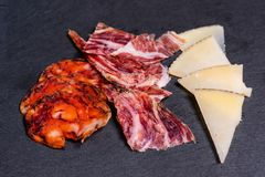 Delicious spanish tapas, appetizer including chorizo, ham, and cheese on black slate royalty free stock image