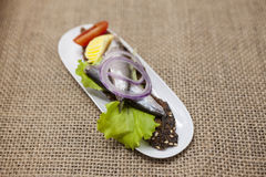 Delicious Spanish tapas with butter and onion salad sprat, Atlantic on slice baguette. An excellent background for the menus, cafe Royalty Free Stock Photo