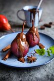 Poached pears in red wine and topped with chocolate sauce. Delicious spiced red wine poached pears topped with chocolate sauce Royalty Free Stock Image