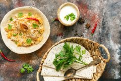 Delicious spicy chicken biryani in ceramic bowl on rustic background with spices, Indian or Pakistani food. Top view
