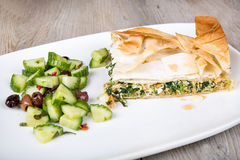 Delicious spinach and feta cheese pie, with filo pastry. Delicious spinach and feta cheese pie, with crispy filo pastry and Greek cucumber salad Stock Photo