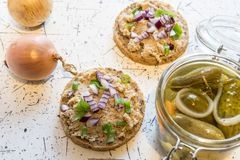 Pork spread, lard and sour cucumbers on fresh round bread, sprinkled with spring and red onion royalty free stock images