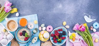 Delicious spring breakfast on a gray stone background. A bouquet of fresh tulips of pink and mint color. Small and large colored. Easter eggs. Oatmeal, biscuits Royalty Free Stock Image