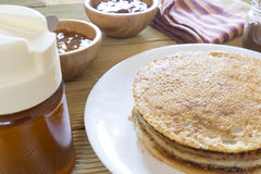 Delicious stack of pancakes with chocolate cream, bowls of jam a Stock Photo