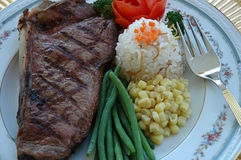 Delicious steak. NewYork steak, rice pilaf, white corn, string beans, broccoli, and a flower made of tomatoe peel Stock Photography