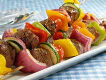 Delicious Steak Kebabs. Juicy steak kebabs with bell peppers, onions, zucchini, and cherry tomatoes stock photo