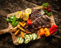 Delicious steakhouse porterhouse steak. And colorful fresh roast vegetables with mangetout peas, corn, zucchini, bell pepper, potato and tomato on a wooden Stock Images